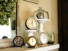 A nice clock grouping ...unique idea of putting a clock on a cake stand with the glass cover. @Kayla Carpenter...what do you think!?