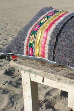 Bijzonder kussen, handgemaakt. Dit kussen is gemaakt van gerecycled materiaal. De basis is een stoere pakdeken met daarin oude truien, dekens, spijkerbroeken of delen van matrassen verwerkt en vervolgens afgewerkt met linten en rijke stoffen.