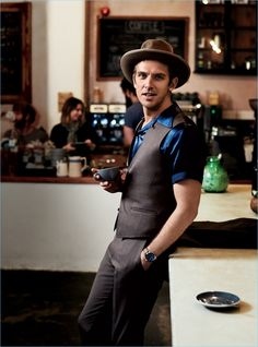 Enjoying a warm beverage at The Fumbally in Dublin, Dan Stevens wears a HUGO Hugo Boss suit with a Visvim shirt, Stetson hat, and Timex watch.