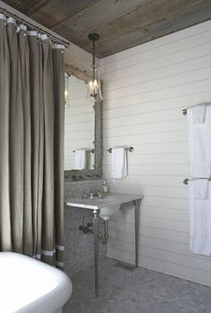 Amazing bathroom with groove walls, plank ceiling, marble top 2-leg washstand vanity, gray mirror, marble herringbone tiles floor, marble tiles backsplash, freestanding tub and gray shower curtain with white ribbon trim.