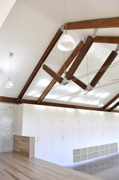 Yass Montessori Preschool, inside the main classroom, on the kids stage, looking up at the tensegrity trusses and softly curved plasterboard ceiling.