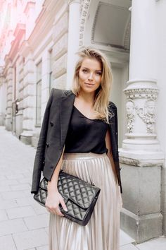 Linda Juhola in black blazer and black top from Zara, pleated rose gold skirt from Zara, Chanel bag and Tamaris shoes