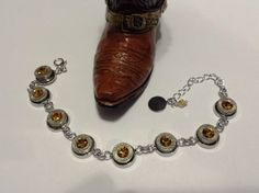 Hornady 9mm Luger bullet tennis bracelet with yellow topaz swarovski crystal gems where the primer was previously located and a yellow swarovski bead at the end of the adjustment chain! Great November birthday gift! Only at AdornmentsByValerie.etsy.com  Check out this item in my Etsy shop https://www.etsy.com/listing/247086136/hornady-9mm-luger-bullet-bracelettennis