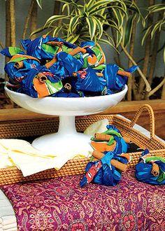 Uma ideia bem bacana é enrolar quadradinhos de bolos ou paçoca em um pedaço de chita bem coloria e uma canela em pau para arrematar!