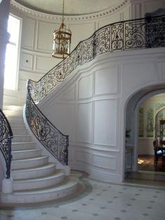 Grand foyer staircase with ornate iron railing