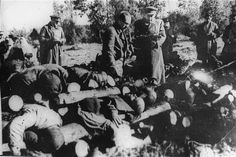 Soviet officials view stacked corpses of victims at the Klooga camp. Due to the rapid advance of Soviet forces, the Germans did not have time to burn the corpses. Klooga, Estonia, 1944.