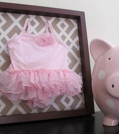 scrapbook paper in shadow box with baby clothes