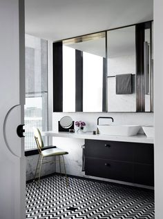 apartment black and white pattern bathroom floor tiles large mirror white glossy ceramic washtafel with black metallic faucet white vintage chair with brass