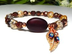 Unique leaf bracelet made with a gorgeous Deep Red Sea Glass focal bead surrounded by 6mm Deep Red with Gold and 8mm Champagne Melon Czech beads, adorned with a Rose Gold Leaf Charm with little handma