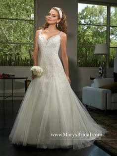 A-line tulle bridal gown with beading detail on sweetheart neckline, shoulder straps, detachable beaded belt, lace applique, chapel train, back zipper with buttons and a long sleeve bolero.