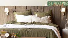 La nature s'invite dans la chambre avec une tête de lit en bois et un linge de lit vert olive ©AMPM