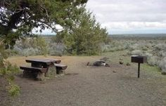 campsite with table, fire pit and cooking grill