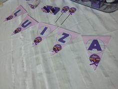 Bandeirinha, molde impresso da internet. Letras confeccionadas com cartolina na cor rocha, colagem de adesivo com o tema da festa.