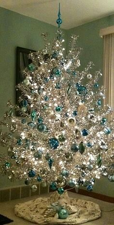 A vintage aluminum tree decorated with blue & silver Shiny Brite ornaments…
