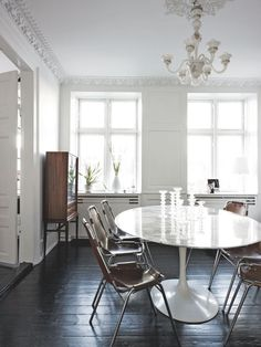 Elegant and personal dining room with a marble dining table and an antique chandelier.