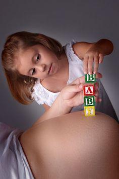 Sibling maternity shot with blocks/lay blocks horizontal with siblings eyes peeking over belly