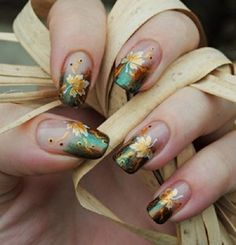 Creative leaf nail art design for the French tip. Give more attitude to your French tips with this gradient and glitter inspired nail polish with golden leaves on top.