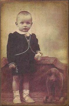 Cute little boy with pull along bear, circa 1910.