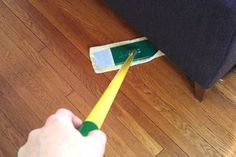 Person Dusting Underneath a Couch | Spring Cleaning Tips