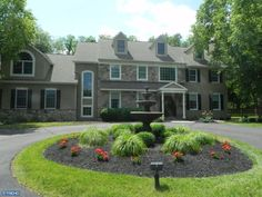 Fountain, arching ornamental grasses, some colorful flowers, turfgrass -- simple, pleasing island in a circle drive.