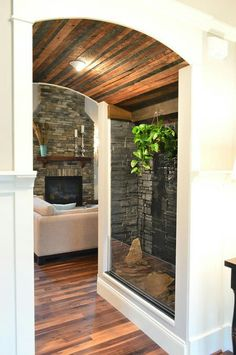 Young House Love | This house has a lot of interesting mixes of materials, like in this little passage between the foyer and the living room that combines a rustic wood ceiling with a stone wall water feature.