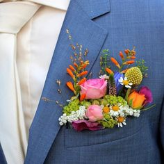The colors are totally off, but I like how this boutonniere looks like a little garden growing outta his pocket. Something like this would be ideal for Tony's.