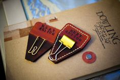 """Leather tabed clips - """"with just a few pieces of scrap leather, cutter and some binder clips.  You decide the size and shape of the leather piece, cut a slit in the middle which should be measured to fit the width of your selected binder clip, or any other types of clip you find pleasing.  Then open and insert the binder clip through the slit, its done."""""""