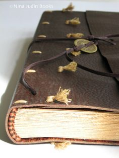 Limp leather binding by Nina Judin. Handmade endbands and closing strap with a coin. 2006.