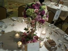 Green, purple, and white floral centerpieces with small lit candles