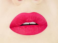 Handmade, vegan, & cruelty-free liquid lipstick in neon red gives a matte, bright red-magenta lip.