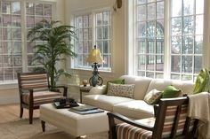 Sunroom Designs. Neutral color theme beautiful sunroom design with nice windows panel, greenery elements, wooden furniture set and cool cream sofa with pop-ups floral green pillows. Warm Refreshment Inside