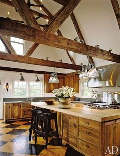 Antique beams crisscross a Nantucket kitchen designed by Karin Blake and the Nantucket Architecture Group. Painted diamonds span the wood floor, and the counters are butcher block.