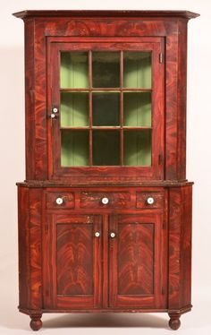 "York County, Grain Paint Corner Cupboard. : Lot 680 York County, PA Federal Grain Paint Decorated Softwood Two-Part Corner Cupboard. A ttributed to John Rupp, Hanover, Pa. Bold grain painted decoration, stepped cornice with single glazed nine pane door above a stepped base with three split dovetailed drawers, two lower paneled doors, molded base and turned feet. 85-1/2""h x 48""w x 22""d. Condition: Very good, some paint loss and wear. Harry Hartman Sold $5000"