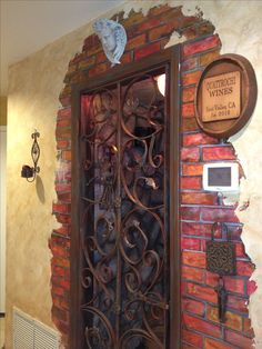 Faux painted brick around wrought iron gate. This used to be a regular white door leading to a utility closet under the stair case. I transformed it into a wine closet.