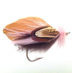 """Fly fishing boutonniere by Blue Spruce Fly Co.  Hand tied fly fishing boutonniere  Style: Lake Dillon  Colors: Brown, tan, pink,   Size: 2"""" Tall, 3"""" Wide  Materials: Feathers  Brooch style pin for easy wear  Custom designs available.  Email BlueSpruceFlyCo@Hotmail.com"""