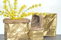 diy | metallic sack. TGtbT.com thinks these would be perfect covering vases, bowls offering irresistible POP items at your consignment shop's check-out. They are JUST what they look like: semi-crumpled paper bags, spray painted (try a MIX of metallics, very chic), rolled down.
