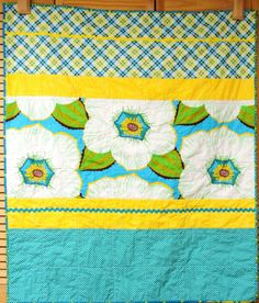 This gorgeous, contemporary quilt features a stunning, large-scale floral and coordinating print from Anna Maria Horners Garden Party fabric line, teamed with yellow stripes, white polka dots on turquoise and a diagonal plaid in green, white. Turquoise, teal, lime, grass greens, yellow and crisp white with a touch of brown and red lend this quilt an ultra-fresh, feminine and elegant air.  I added two rows of rick rack- one turquoise and one yellow. I bound the quilt in a coordinating print…