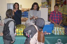 US First Lady Michelle Obama and her daughters Malia and Sasha distribute food at 'Bread for the City' on November 26 2014 in Washington DC Bread for...
