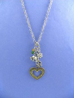 Adorable 30 inch Long Charm Necklace Sigma Alpha OFFICIALLY LICENSED PRODUCT.  Long Charm Necklace is a perfect gift for any Sigma Alpha sorority member...its really cute! Necklace features the colors and symbols of the sorority.  Gold decorative open heart (1 1/4 diameter) is surrounded by a smaller silver baby bull (3/4 W x 1/2L), a decorative silver flower charm, a small LOVE charm and an emerald and maize Swarovski bead strand. Charms are hung artistically for visual intere...
