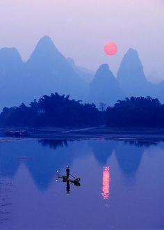 A Cormorant Fisherman at sunset on the Li River near Xing Ping.  Guangxi Province – Southern China.  Photograph by Michael Sheridan