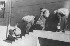 A family of Macedonian Jews carries their luggage down a flight of stairs as they leave the Tobacco Monopoly transit camp for the deportation trains to killing camps. Skopje, Yugoslavia, March 11-29, 1943.