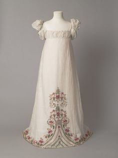 1812-1815 - England - Girl's dress of white muslin embroidered from the hem with a floral design in coloured wools. The dress has a high-waisted bodice, vertically-gathered puffed sleeves and a trained skirt.  Muslin embroidered in wool
