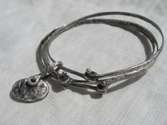 Triple riveted bangles with pebble charm by LisaColbyMetalsmith, $220.00