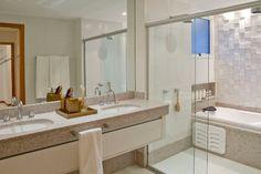 Decoração banheiro - Mais um projeto em tons neutros com bancada em granito cinza claro e paredes brancas. Destaque para a parede do fundo com o revestimento etrusco da marca Castellato