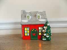 Cute bright red ceramic lighted village house. I believe it was made by Pacific Rim although the box it came with does not match the house. It seems to be in good used vintage condition. I believe I spotted 3 small paint rubs on 3 different windows....or it could just be white paint residue from the manufacturer. Im not sure but would like to bring it to the buyers attention. Pictures show it turned on. Everything is operational with the house and its ready to be displayed. :)  Measures…