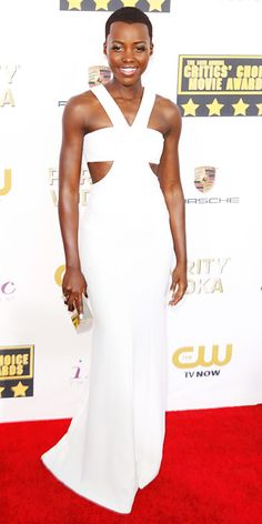Lupita Nyong'o wearing a custom ivory silk crepe bandeau Calvin Klein Collection dress, with a gold box clutch by the same label.