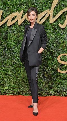 Victoria Beckham wears a black top, tuxedo blazer, skinny tuxedo pants, and black heels