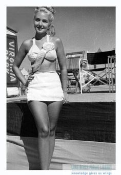 Pike, Long Beach, 1949. A beauty pageant contestant wears a two-piece swimsuit and with a large pageant ribbon rosette pinned to the top. She poses in front of an elevated stage at the Pike. Directors' style outdoor chairs are set up on the stage above and behind her. For information about copyright and ordering images from the LBPL Digital Archive, see http://www.lbpl.org/history.