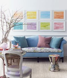 A canvas of bright white is a flattering and soothing backdrop for a palette of pastel colors. Carefully placed pops of color, such as the grouping of oceanic paintings and the array of colorful fabric, invigorate the space without overstimulating. Soothing seat for an everyday retreat.