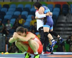 Sara Dosh (JPN) celebrates her victory over Natalia Vorobeva (RUS), foreground, in a women's freestyle 69kg wrestling gold medal match at Carioca Arena 2 during the Rio 2016 Summer Olympic Games.